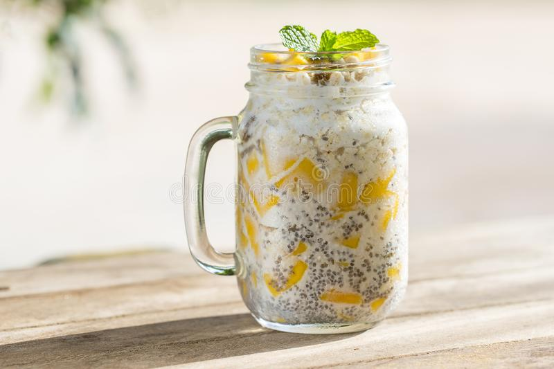 Healthy food, chia seed pudding with mango, oat flakes, coconut milk and muesli, vitamin breakfast in glass mug. Morning in Thaila. Nd. Close up stock images