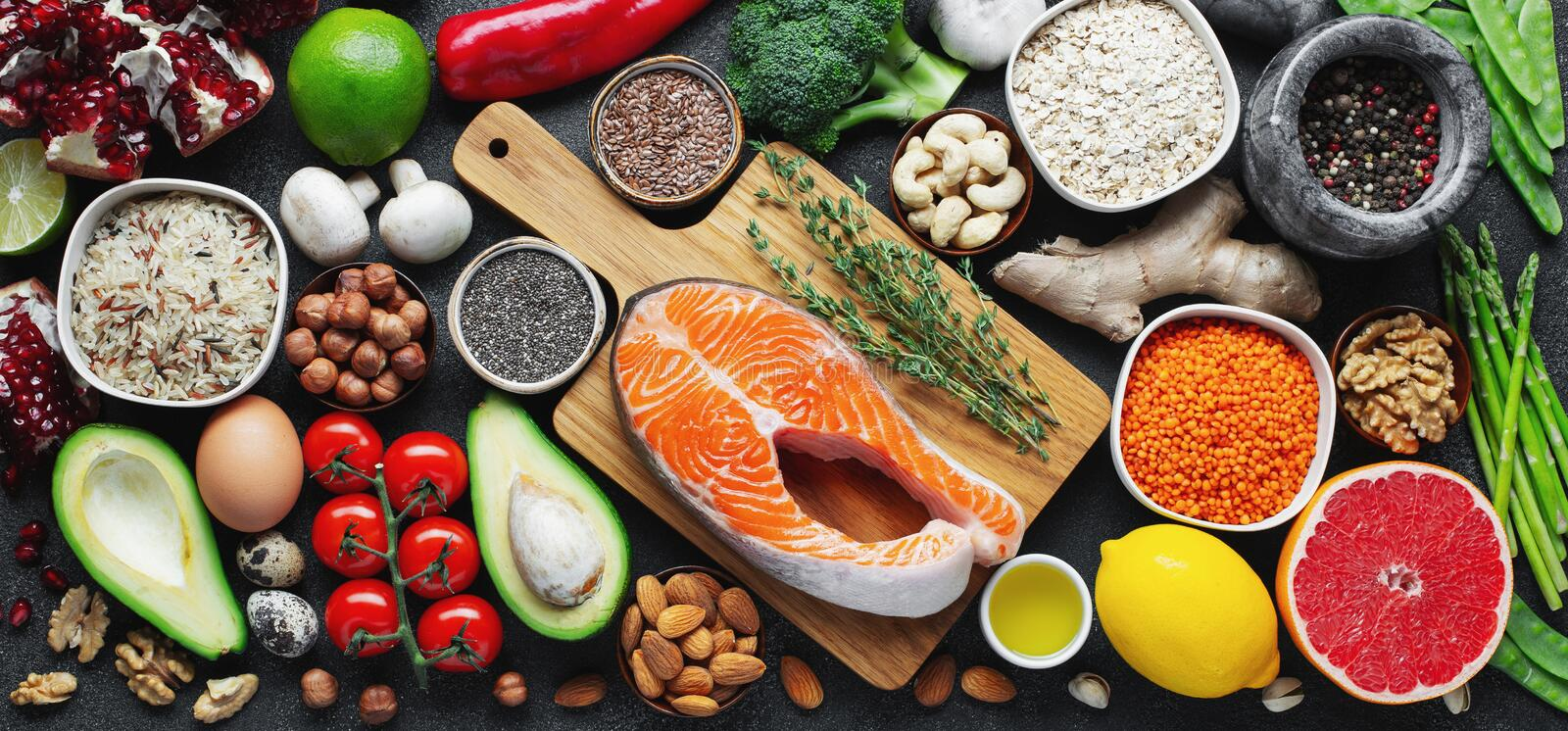 Healthy food clean eating selection: fish, fruit, nuts, vegetable, seeds, superfood, cereals, leaf vegetable on black concrete stock photo