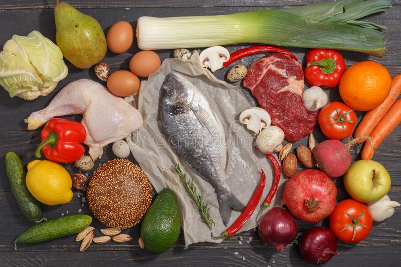 Healthy food clean eating selection: fruit, vegetable, seeds, fish, meat, leaf vegetable on wooden background. Top view. Organic fresh vegetables avocado tomato royalty free stock image