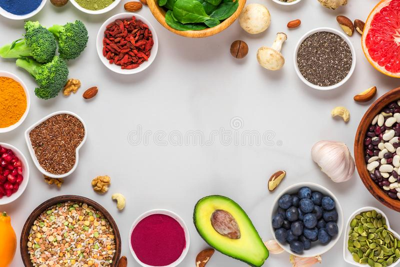 Healthy food clean eating selection: fruit, vegetable, seeds, superfood, nuts, berries on white marble background stock photo