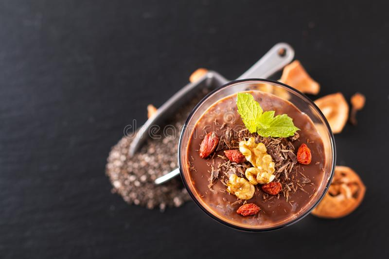 Healthy food concept Chia seeds, chocolate milk pudding with goji and dried walnuts in small Glass on black slate board background royalty free stock images