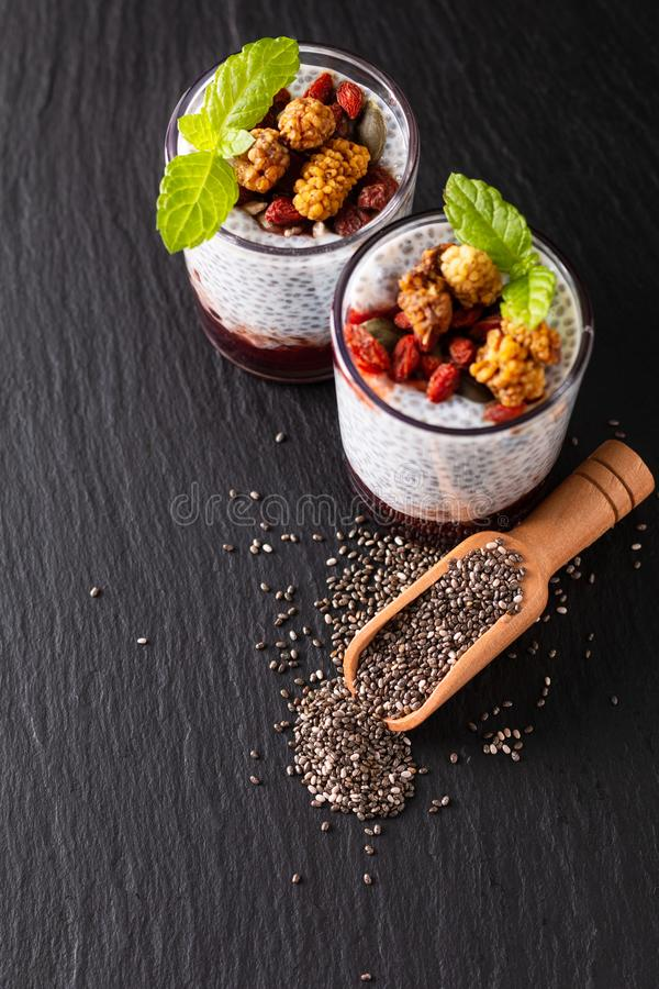 Healthy food concept Chia seeds, milk pudding with goji, white mulberry and mix dried seeds in small Glass on black slate board stock image