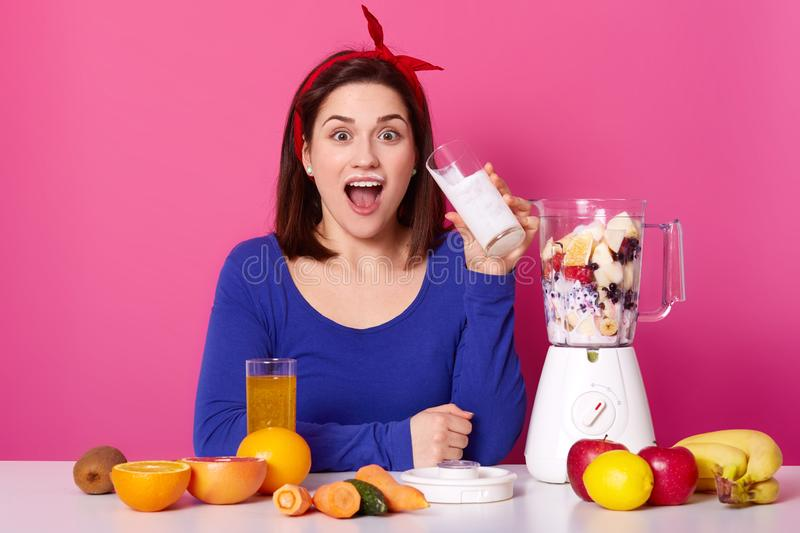 Healthy food concept. Close up of a young woman uses berries and bananas for making smoothie. Astonished lady againest pink studio royalty free stock photo