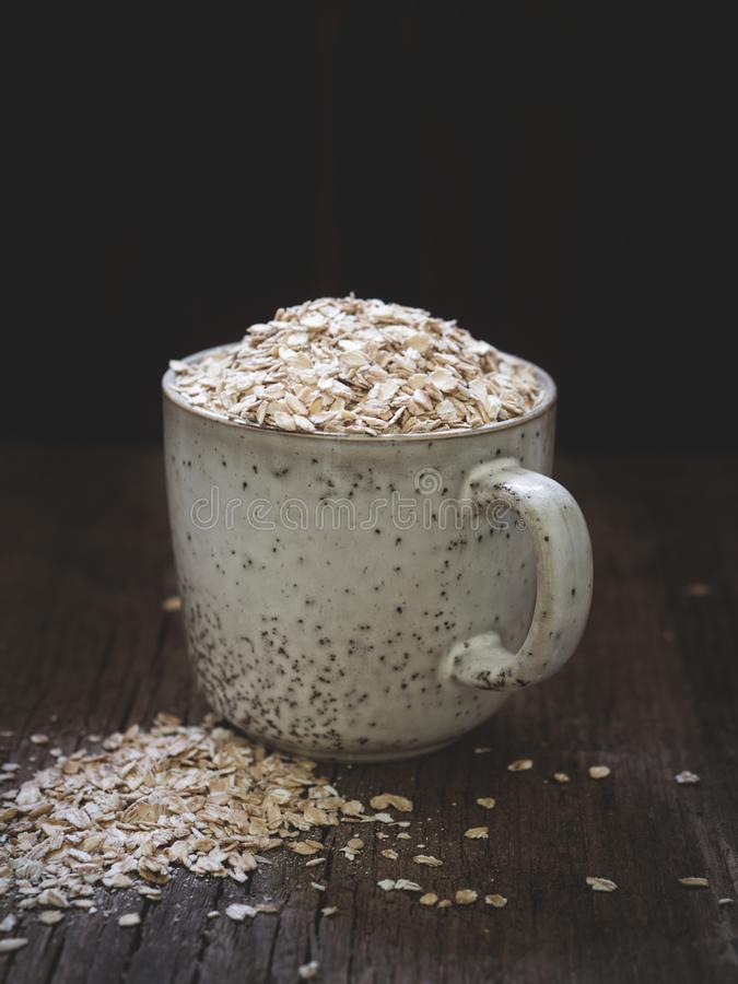 Healthy food concept. Dry oat flakes spilled from a gray ceramic cup onto a wooden table. Closeup.  royalty free stock image