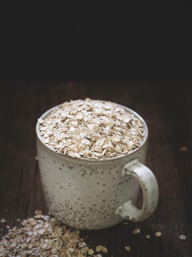 Healthy food concept. Dry oat flakes spilled from a gray ceramic cup onto a wooden table. Closeup.  royalty free stock photography