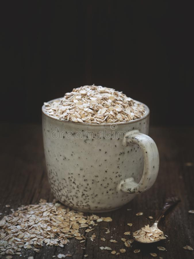 Healthy food concept. Dry oat flakes spilled from a gray ceramic cup onto a wooden table. Closeup.  royalty free stock photos