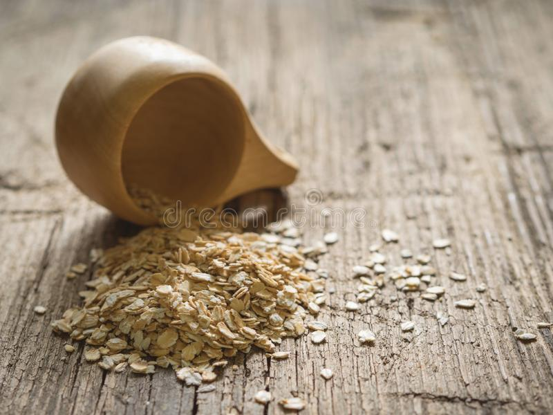 Healthy food concept. Dry oat flakes spilled from a wooden cup onto a wooden table. Closeup.  stock photography