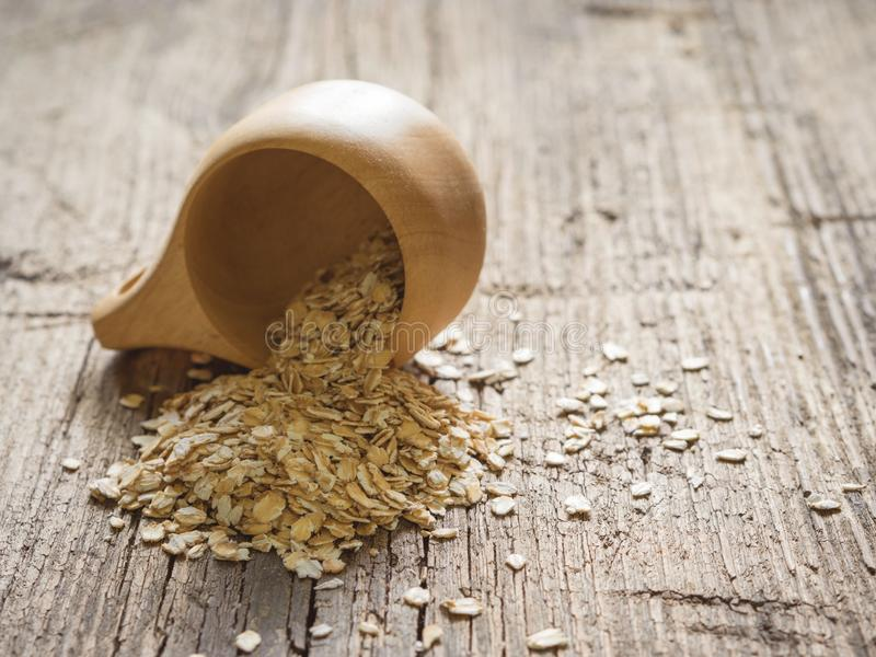 Healthy food concept. Dry oat flakes spilled from a wooden cup onto a wooden table. Closeup.  stock photos