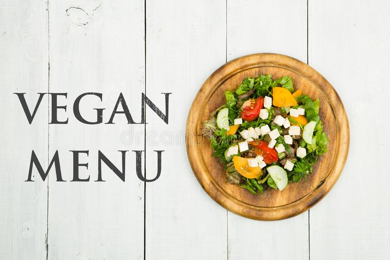 Healthy food concept - Fresh vegetable salad with greenery, tofu, tomatoes, cucumber and text Vegan menu stock photos