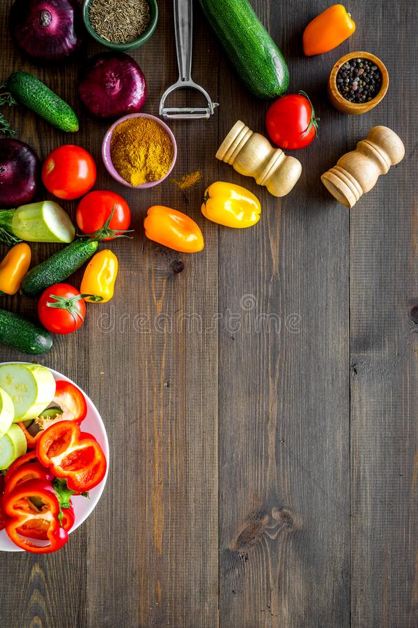 Healthy food concept. Ingredients for vegetable stew. Squash, bell pepper, tomato, spices, oil on dark wooden background. Top view stock photos