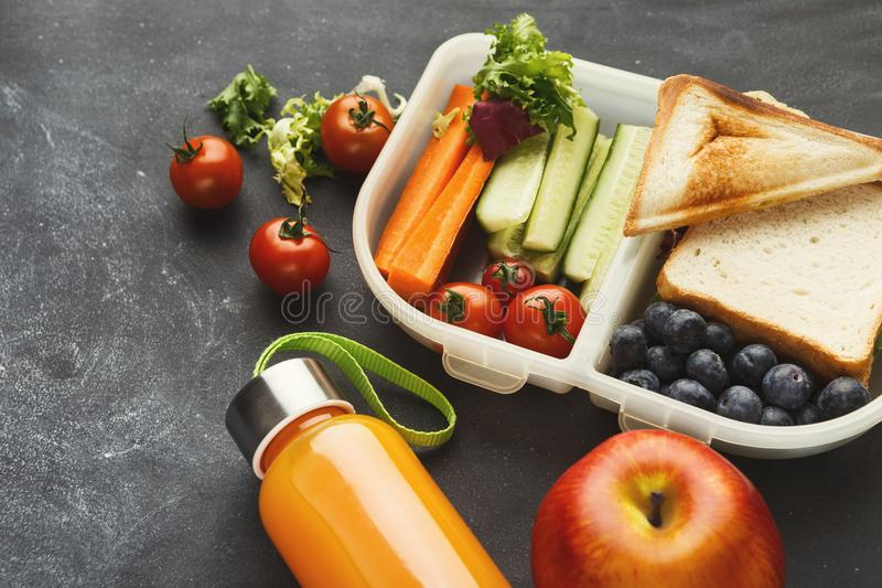 Lunch box with healthy food on black table background royalty free stock photography