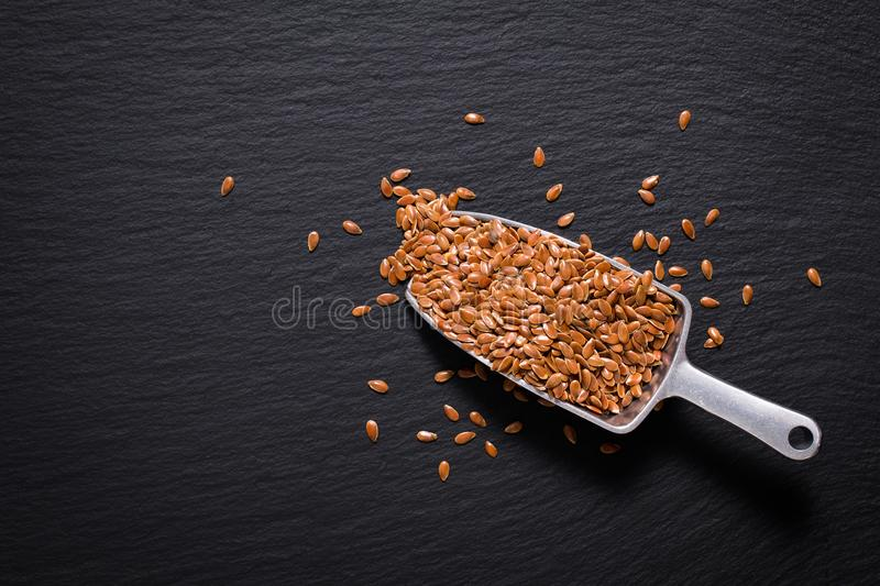 Healthy food concept Organic Flax seeds on black slate stone plate royalty free stock image