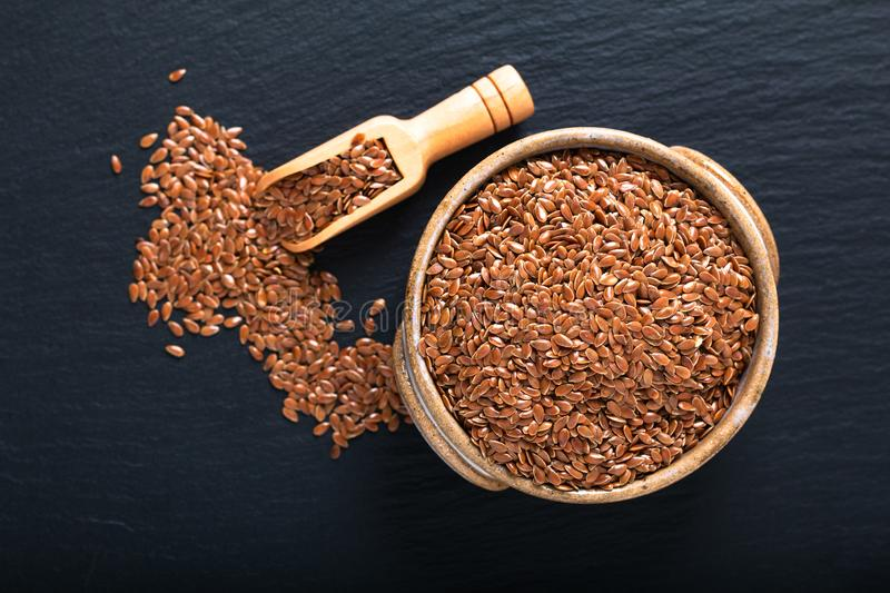 Healthy food concept Organic Flax seeds in ceramic bolw on black slate board with copy space royalty free stock image