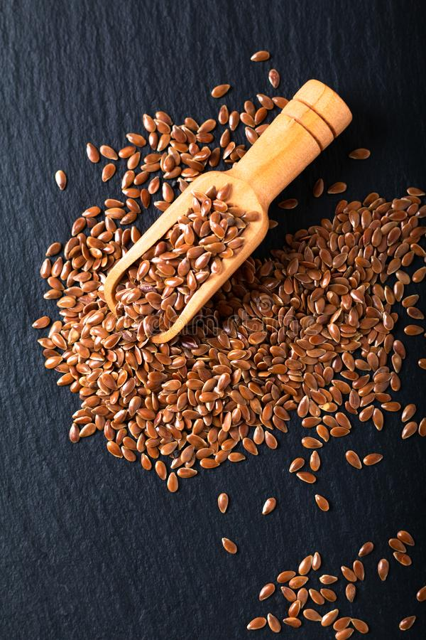 Healthy food concept Organic Flax seeds in wood scoop on black slate board with copy space royalty free stock photography