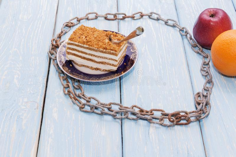 Healthy food concept, a piece of cake on a wooden table is surrounded by an iron chain. stock photos