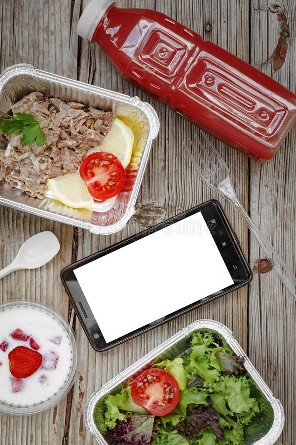 Healthy food. Concept: Proper nutrition, catering, business lunch. Smartphone, wholesome food, disposable containers royalty free stock image