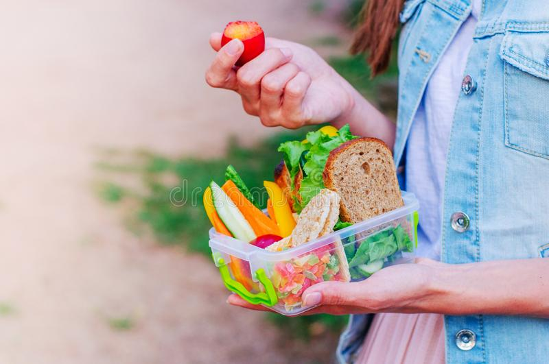 Young hipster girl eating from lunch box outdoor royalty free stock images