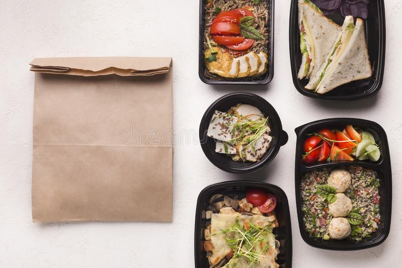 Healthy food delivery in black boxes ready to be send. In paper bag, copy space stock photos