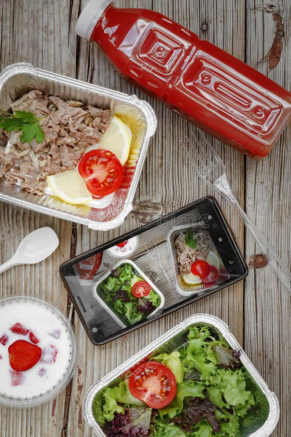 Healthy food delivery. Concept: Proper nutrition, catering, business lunch. Smartphone, wholesome food, disposable royalty free stock photo