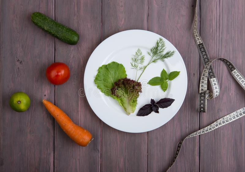 Healthy food and diet vegetarian concept - measure tape, white plate with leaf of salad, cucumber, tomato and other vegetables royalty free stock photo