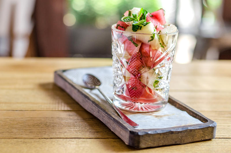 Healthy food. Dietary salad from watermelon and melon with mint, in a glass, on a wooden stand royalty free stock photos
