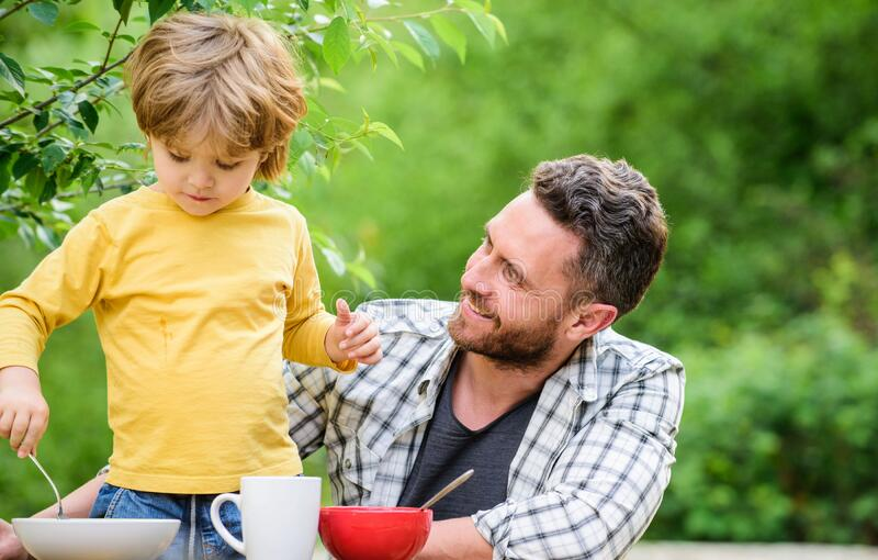 Healthy food and dieting. Childrens day. summer picnic. Morning breakfast. father and son eating outdoor. happy fathers royalty free stock photo