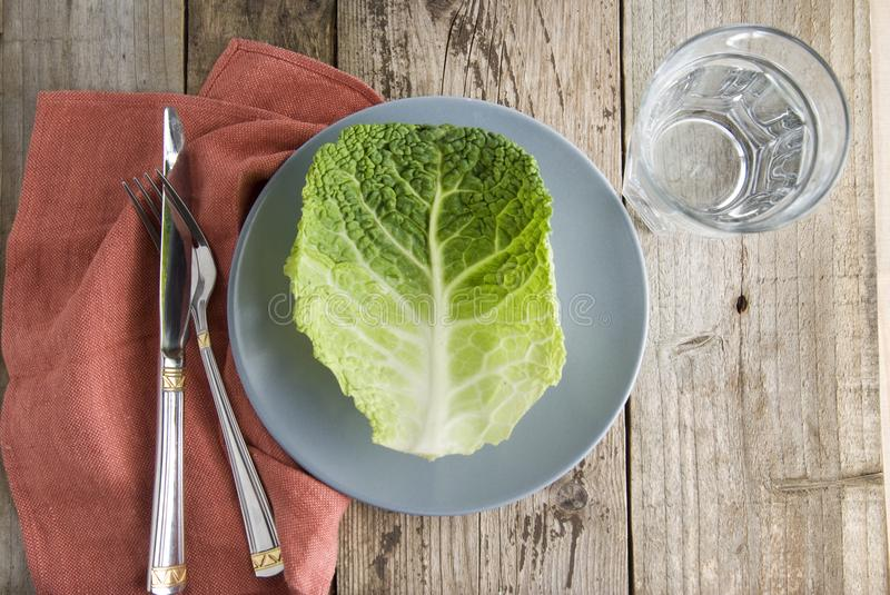Healthy food and dieting concept. One brassica leaf isolated in grey plate, with fork and knife, over rustic wooden background. Be royalty free stock photo