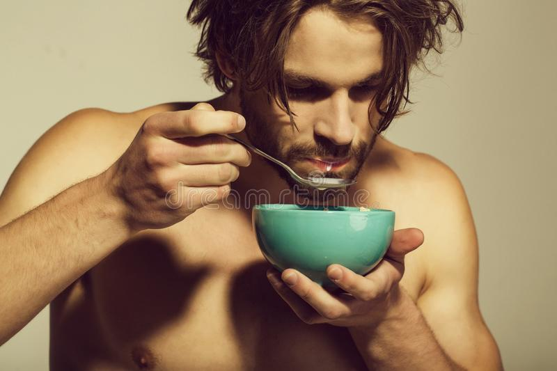 Healthy food and dieting, fitness, morning. man with bare chest eating breakfast of oatmeal with milk. In bowl with spoon on grey background royalty free stock photos