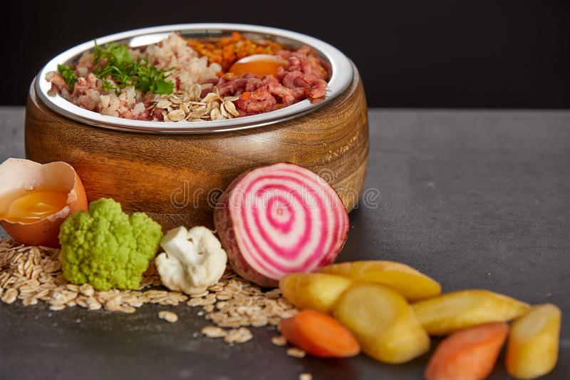 Healthy food for dogs concept. Healthy barf food for dogs concept with mix of fresh vegetables and meat in wooden bowl, viewed in close-up royalty free stock photos