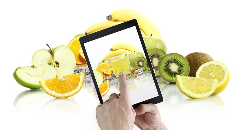 Healthy food eating and balanced diet concept, hand pointing juice glass on digital tablet screen with fruits background royalty free stock photo