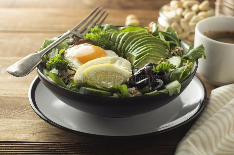 Healthy food. Eggs, quinoa, avocado, green salad, black olives. Wooden table. diet, lose weight. Healthy food. Eggs, quinoa, avocado, green salad, black olives stock images