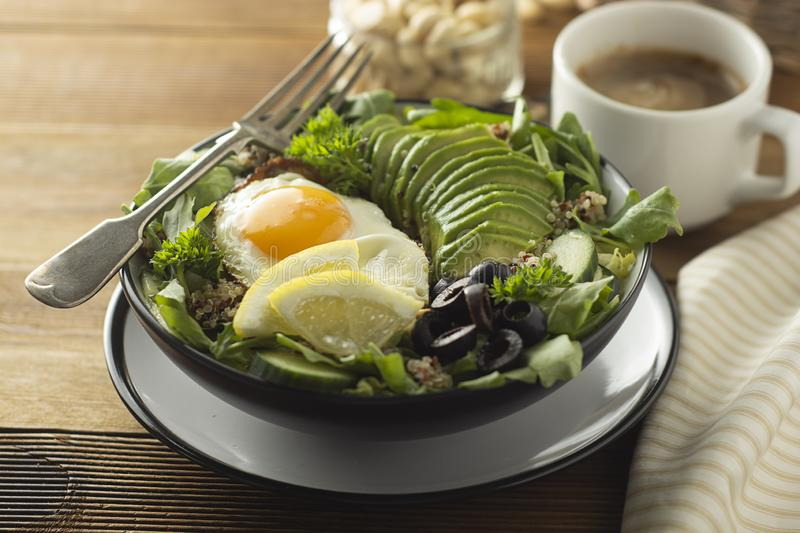 Healthy food. Eggs, quinoa, avocado, green salad, black olives. Wooden table. diet, lose weight. Healthy food. Eggs, quinoa, avocado, green salad, black olives stock photos
