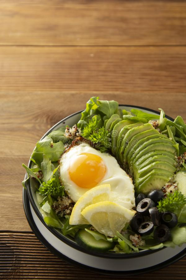 Healthy food. Eggs, quinoa, avocado, green salad, black olives. Wooden table. diet, lose weight. Healthy food. Eggs, quinoa, avocado, green salad, black olives stock photo
