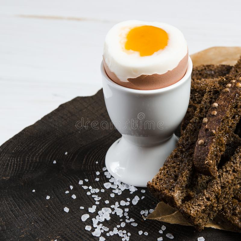 Healthy food. English breakfast with boiled egg and croutons on a white wood background stock image