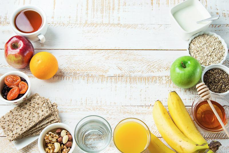 Healthy Food Fiber Sources Breakfast Oatmeal Honey Fruits Apples Banana Orange Juice Water Green Tea Nuts. White Plank Wood Table. Semi Circle Border royalty free stock image