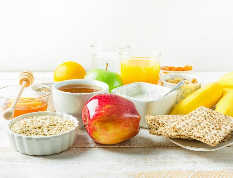 Healthy Food Fiber Sources Breakfast Oats Honey Fruits Apples Banana Orange Juice Water Green Tea Nuts. White Plank Wood Table. Bright Morning Sunlight Cozy stock images