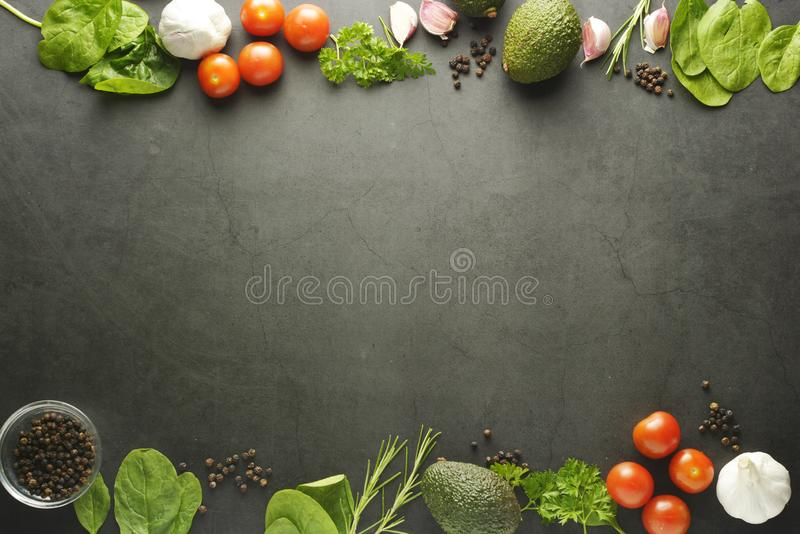 Healthy food frame mockup. Dark background with copy space with spices, vegetables - avocado, spinach, tomatoes. Flat lay stock images