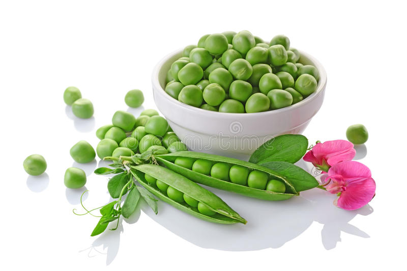 Healthy food. Fresh green peas in white bowl with pink flowers of sweet pea royalty free stock photos