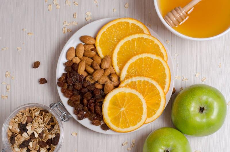 Healthy food. Fruit, homemade granola, nuts, honey on a white ta stock photos