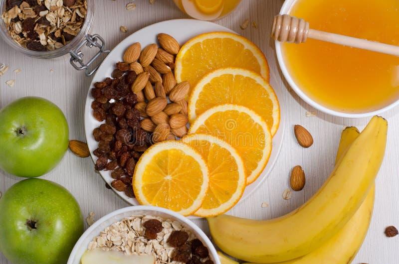 Healthy food. Fruit, homemade granola, nuts, oatmeal, honey, ora stock photography