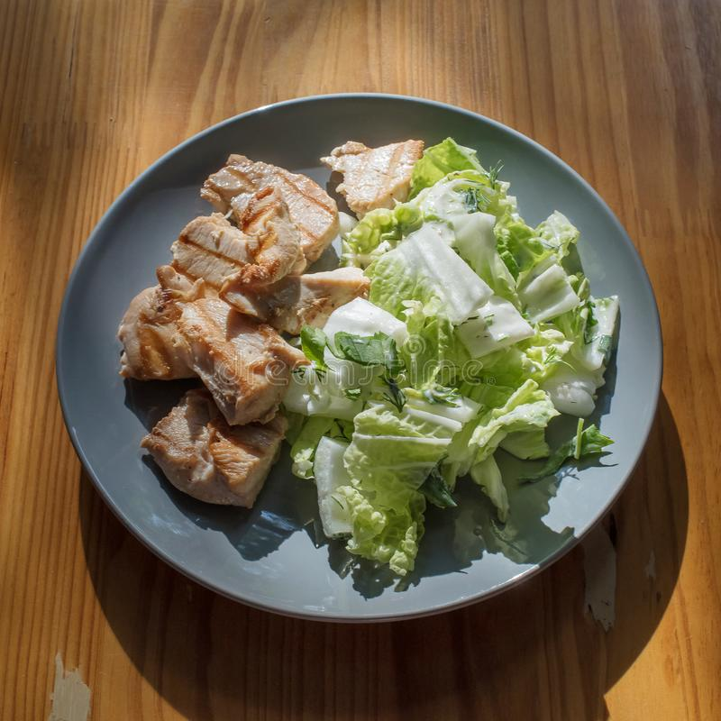 Healthy food: grilled chicken and Peking salad with greens on a gray plate in the sun on a wooden table stock images
