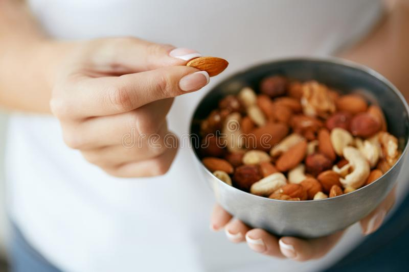 Healthy Food. Hands Holding Bowl With Nuts. Close Up Of Female Holding Plate With Different Types Of Nuts. Healthy Fats For Nutrition And Diet. High Quality royalty free stock image