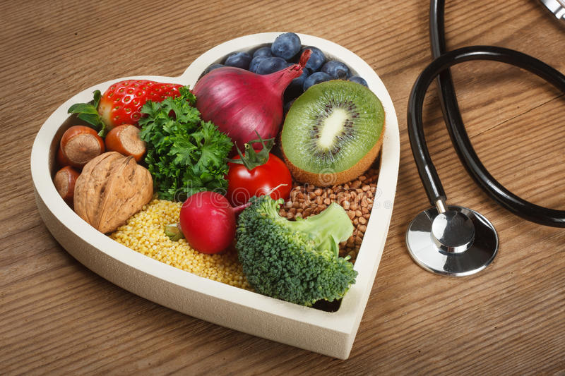 Healthy food in heart shaped bowl. And stethoscope. Food such as blueberries, red onion, strawberry, parsley leaves, hazelnuts, walnut, tomato. kiwi, millet royalty free stock image