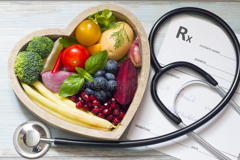 Healthy food in heart stethoscope and medical prescription diet and medicine concept. Closeup stock image