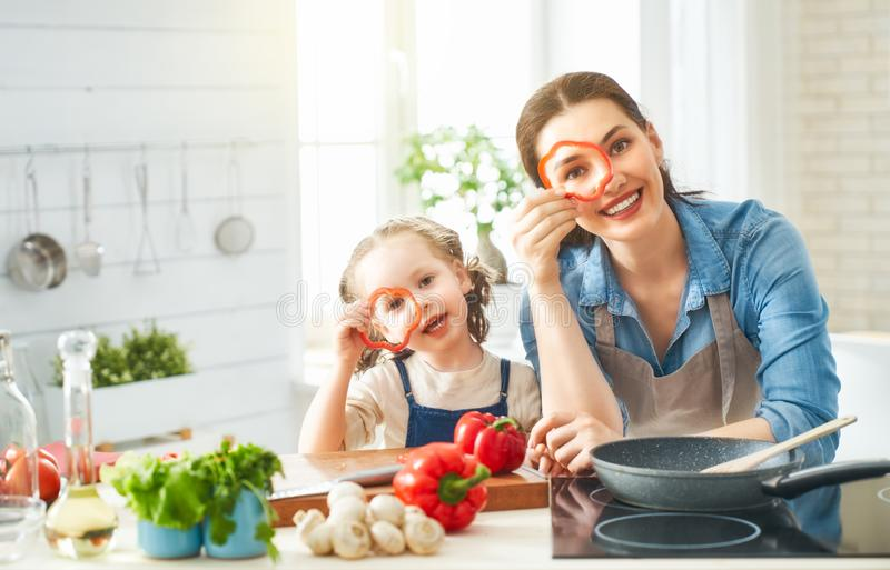 Happy family in the kitchen. Healthy food at home. Happy family in the kitchen. Mother and child daughter are preparing proper meal royalty free stock image