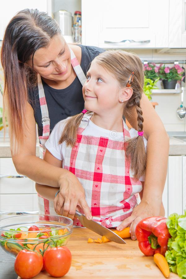 Happy family in the kitchen. Mother and child daughter are preparing the vegetables royalty free stock photos