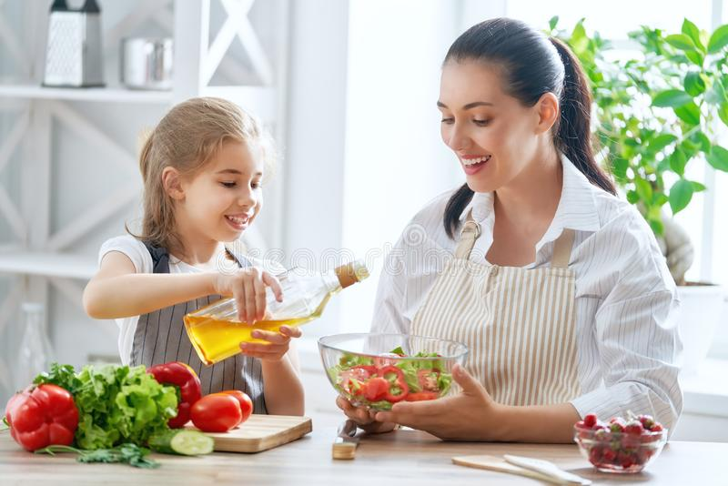 Happy family in the kitchen. Healthy food at home. Happy family in the kitchen. Mother and child daughter are preparing the vegetables stock image
