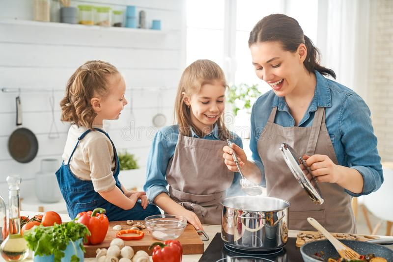Happy family in the kitchen. Healthy food at home. Happy family in the kitchen. Mother and children daughters are preparing vegetables stock photo