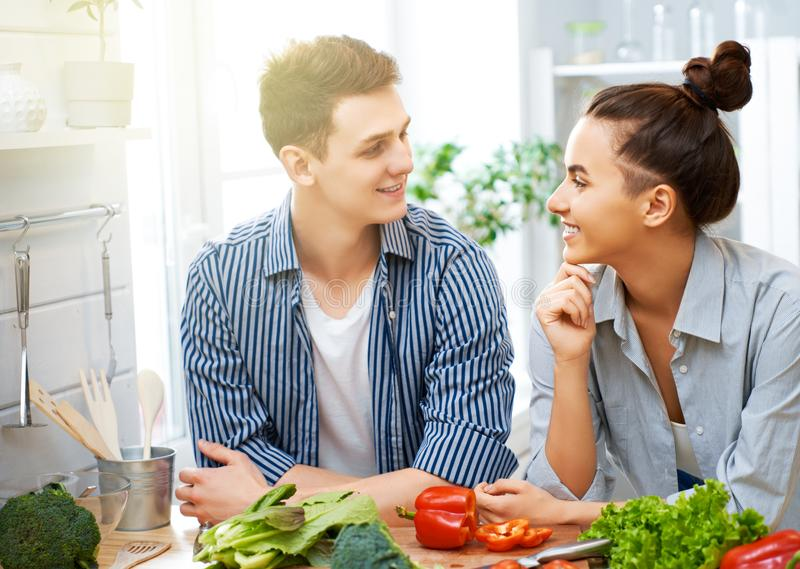 Loving couple is preparing the proper meal. Healthy food at home. Happy loving couple is preparing the proper meal in the kitchen stock photography