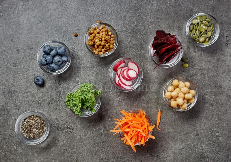 Healthy food ingredients. Bowls of healthy food ingredients on grey table, top view stock image